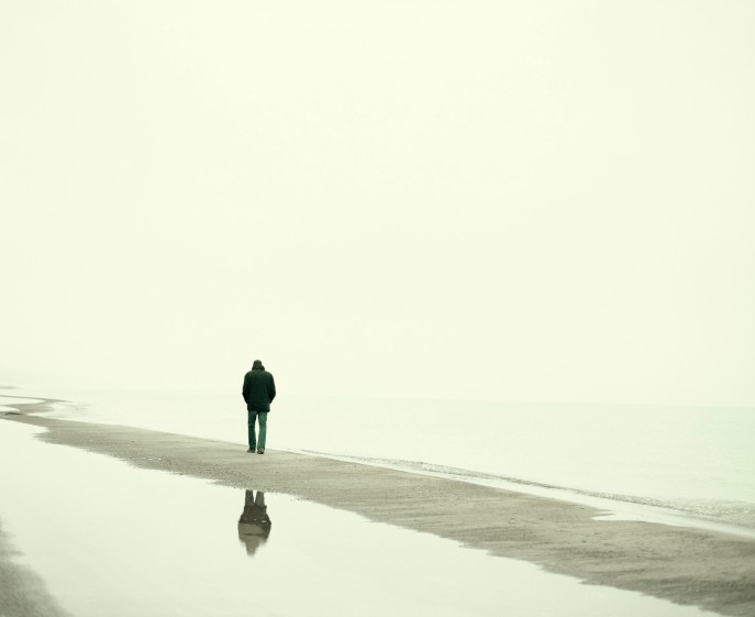 Man walking on beach in winter
