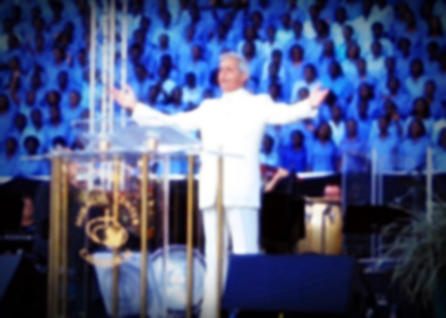 """26 Jun 2007, Kampala, Uganda --- Televangelist Benny Hinn leads prayers at Uganda's national stadium in Kampala May 19, 2007. Wearing a white suit shimmering in the flood lights, the preacher promised a """"miracle crusade"""" to heal the sick, make the blind see and the lame walk.   --- Image by © Tim Cocks/X01722/Reuters/Corbis"""